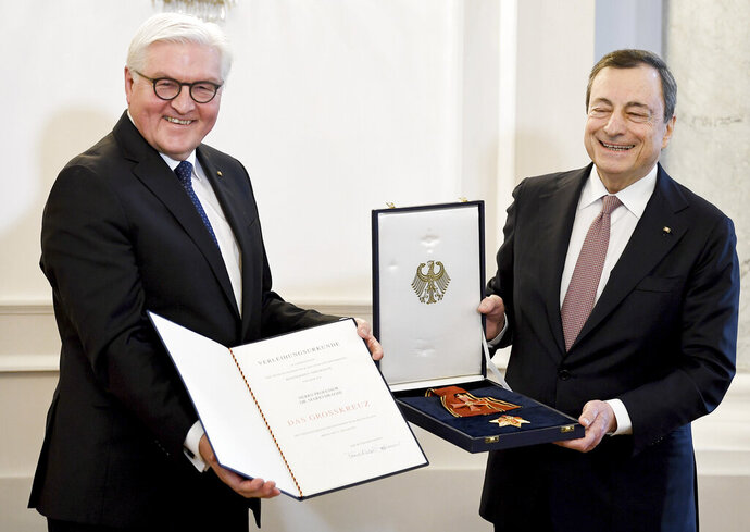 German President Frank-Walter Steinmeier, left, and the former President of the European Central Bank (ECB), Mario Draghi, right, pose for the media at the Bellevue Palace in Berlin, Germany, Friday, Jan. 31, 2020. Mario Draghi has been awarded Germany's highest honor. It was a recognition of his central role in helping preserve Europe's single currency that has met with some criticism in the eurozone's biggest economy.  (Britta Pedersen/dpa via AP)
