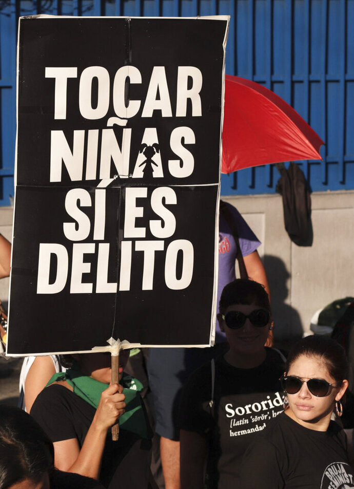 In this Nov. 4, 2019 photo, a woman holds a sing that reads in Spanish: