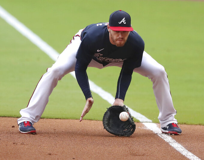 Atlanta Braves first baseman Freddie Freeman fields a ground ball by Yonder Alonso and tags first for the out during the second inning of an intrasquad game Saturday, July 18, 2020, in Atlanta.  It was Freeman's fist game since his battle with Covid-19. (Curtis Compton/Atlanta Journal-Constitution via AP)