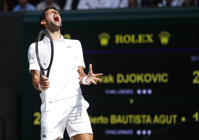 Serbia's Novak Djokovic reacts as he plays against Spain's Roberto Bautista Agut in a Men's singles semifinal match on day eleven of the Wimbledon Tennis Championships in London, Friday, July 12, 2019. (Carl Recine/Pool Photo via AP)