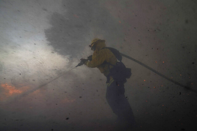 FILE - In this Monday, Oct. 26, 2020 file photo, A firefighter battles the Silverado Fire in Irvine, Calif. Two firefighters who were critically burned while trying to set backfires to slow the spread of a Southern California wildfire in October likely shouldn't have been there in the first place given the extraordinarily dangerous conditions, according to a newly released investigation of the incident.(AP Photo/Jae C. Hong, File)