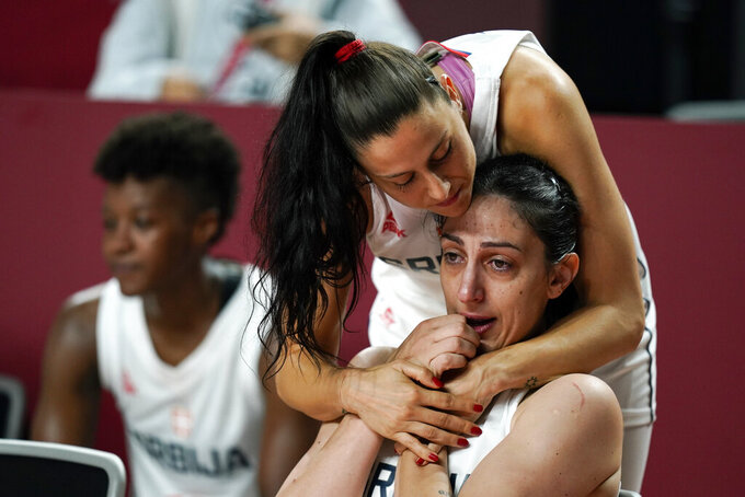 Serbia's Jelena Brooks gets a hug from teammate Sasa Cado after the women's basketball bronze medal game against France at the 2020 Summer Olympics, Saturday, Aug. 7, 2021, in Saitama, Japan. (AP Photo/Charlie Neibergall)