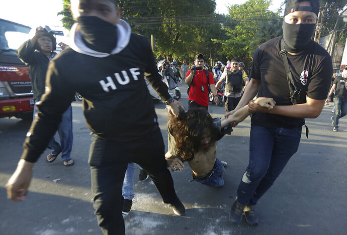 Plain-clothed police officers arrest a student protester during a rally in Makassar, South Sulawesi province, Indonesia, Thursday, Sept. 26, 2019. Protests continue in several cities in the country as students rallied against a new law that critics say cripples the country's anti-corruption agency. (AP Photo/Bahauddin Raja Baso)