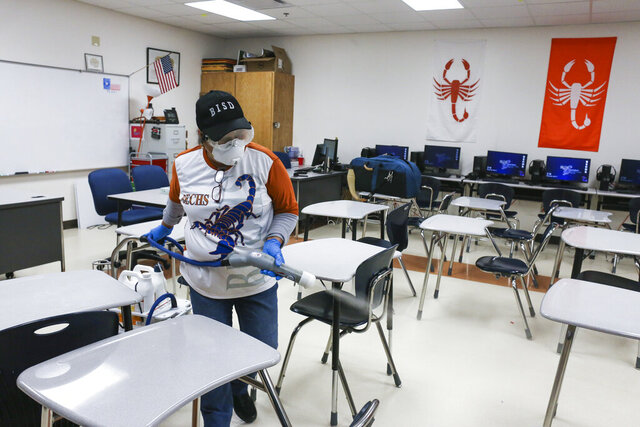 FILE - In this Wednesday, March 11, 2020, file photo, custodial staffer Hortensia Salinas uses an Electrostatic Clorox Sprayer to spray disinfectant in a classroom at Brownsville Early College High School in Brownsville, Texas. Closing schools to combat the spread of the coronavirus is having a sweeping impact on an annual rite of spring: the standardized tests that are dreaded by millions of students and teachers alike. (Denise Cathey/The Brownsville Herald via AP, File)