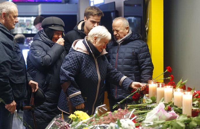 Relatives of one of the flight crew members of the Ukrainian 737-800 plane that crashed on the outskirts of Tehran, stand at a memorial inside Borispil international airport outside Kyiv, Ukraine, Saturday, Jan. 11, 2020. Ukraine's President Volodymyr Zelenskiy says that Iran must take further steps following its admission that one of its missiles shot down Ukrainian civilian airliner. (AP Photo/Efrem Lukatsky)