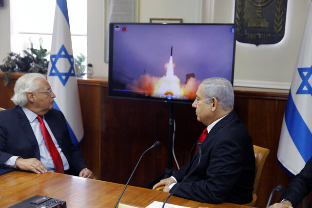 FILE - In this July 28 2019 file photo, Israeli Prime Minister Benjamin Netanyahu, right, and US Ambassador to Israel David Friedman watch a video which shows the launch of the Arrow 3 hypersonic anti-ballistic missile during a cabinet meeting in Jerusalem. Israel's Defense Ministry said, Tuesday, Dec. 15, 2020, that it has successfully conducted a series of live fire drills to test its three missile defense systems. It has developed and tested the Arrow 3, David's Sling and Iron Dome in conjunction with the United States. (Menahem Kahana/Pool  via AP, File)