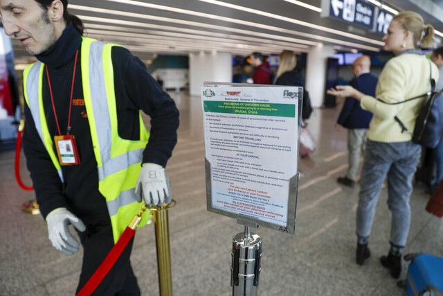 A notice explaining precautions to be taken by people traveling to Wuhan, China, is seen at a terminal of Rome's International Fiumicino airport, Tuesday, Jan. 21, 2020. Heightened precautions are being taken worldwide as a new strain of coronavirus has been infecting hundreds of people across the central Chinese metropolis. (AP Photo/Gregorio Borgia)