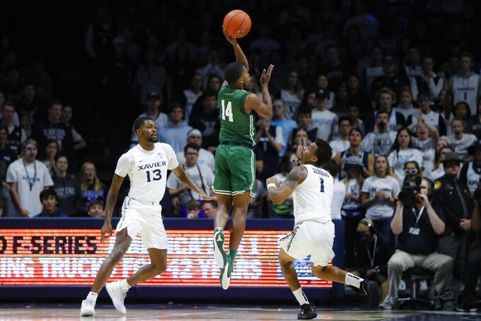 Jacksonville's Mo Arnold (14) shoots against Xavier's Naji Marshall (13) and Paul Scruggs (1) during the second half of an NCAA college basketball game Tuesday, Nov. 5, 2019, in Cincinnati. (AP Photo/John Minchillo)