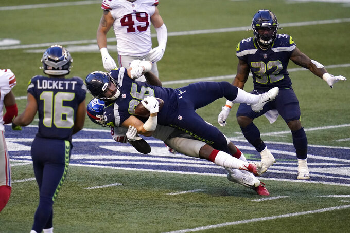 Seattle Seahawks tight end Jacob Hollister (86) is brought down by New York Giants linebacker Tae Crowder (48) during the second half of an NFL football game, Sunday, Dec. 6, 2020, in Seattle. (AP Photo/Elaine Thompson)