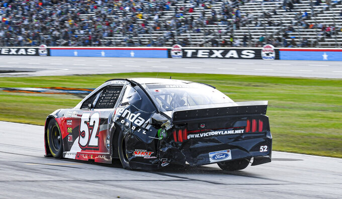 Garrett Smithley (52) drives down pit road after hitting the wall during a NASCAR Cup Series auto race at Texas Motor Speedway, Sunday, Nov. 3, 2019, in Fort Worth, Texas. (AP Photo/Randy Holt)