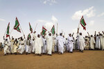 A crowd gathers as Gen. Mohammed Hamdan Dagalo, the deputy head of the military council, speaks during a military-backed tribe's rally, in the Nile River State, Sudan, Saturday, , on July 13, 2019. . (AP Photo/Mahmoud Hjaj)