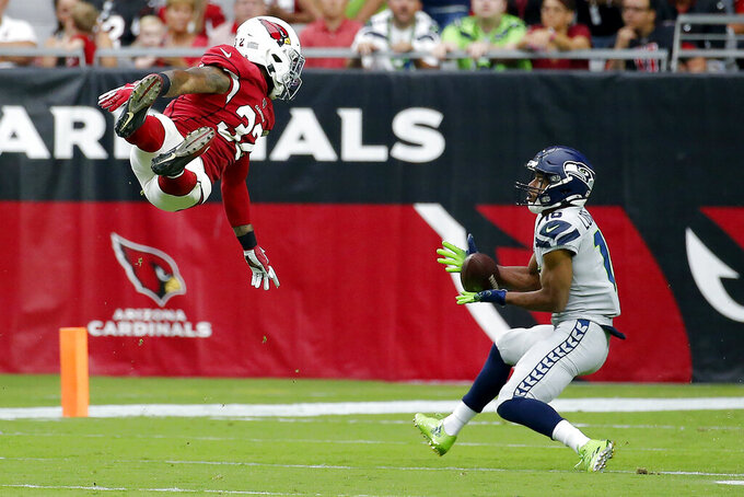 Seattle Seahawks wide receiver Tyler Lockett (16) makes the catch as Arizona Cardinals strong safety Budda Baker (32) defends during the first half of an NFL football game, Sunday, Sept. 29, 2019, in Glendale, Ariz. (AP Photo/Rick Scuteri)