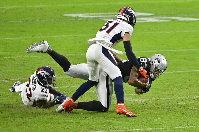 Las Vegas Raiders tight end Darren Waller (83) is taken down by Denver Broncos strong safety Kareem Jackson (22) and free safety Justin Simmons (31) during the second half of an NFL football game, Sunday, Nov. 15, 2020, in Las Vegas. (AP Photo/David Becker)