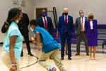 President Joe Biden and first lady Jill Biden observe a physical education class together with school principal Kerry Richardson, left, and Secretary of Education Miguel Cardona, second from right, during a visit at Brookland Middle School in northeast Washington, Friday, Sept. 10, 2021. Biden has encouraged every school district to promote vaccines, including with on-site clinics, to protect students as they return to school amid a resurgence of the coronavirus. (AP Photo/Manuel Balce Ceneta)
