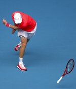 Canada's Denis Shapovalov throws his racket in frustration during his first round singles match against Hungary's Marton Fucsovics at the Australian Open tennis championship in Melbourne, Australia, Monday, Jan. 20, 2020. (AP Photo/Dita Alangkara)