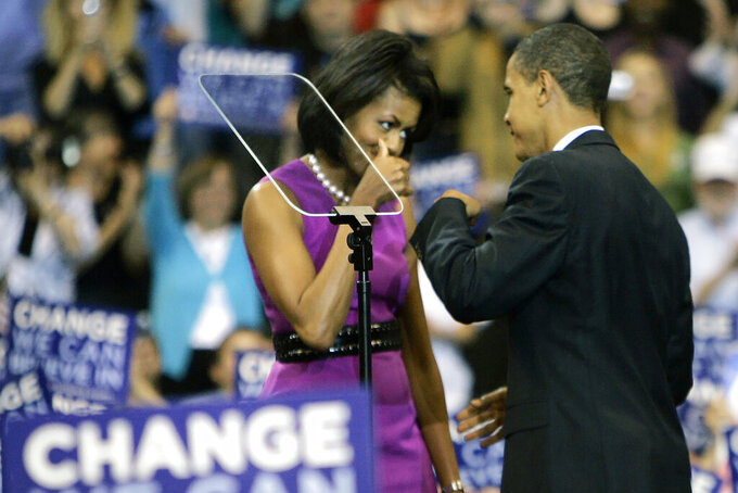 FILE - This June 3, 2008, file photo shows then Democratic presidential candidate Sen. Barack Obama fist bump with his wife Michelle, before speaking at a primary night rally in St. Paul, Minn. Barack and Michelle Obama famously fist-bumped when he clinched the Democratic presidential nomination in June 2008, making the move very cool in some circles, causing outrage in others. (AP Photo/Morry Gash, File)