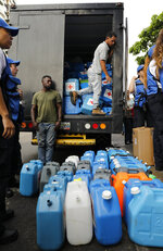 Empty water containers to be handed out with purification pills are lined up during the Red Cross' first aid shipment in Caracas, Venezuela, Tuesday, April 16, 2019. In late March, the Red Cross federation announced it would soon begin delivering assistance to an estimated 650,000 people and vowed that it would not accept interference from either side of the polarized country. (AP Photo/Ariana Cubillos)