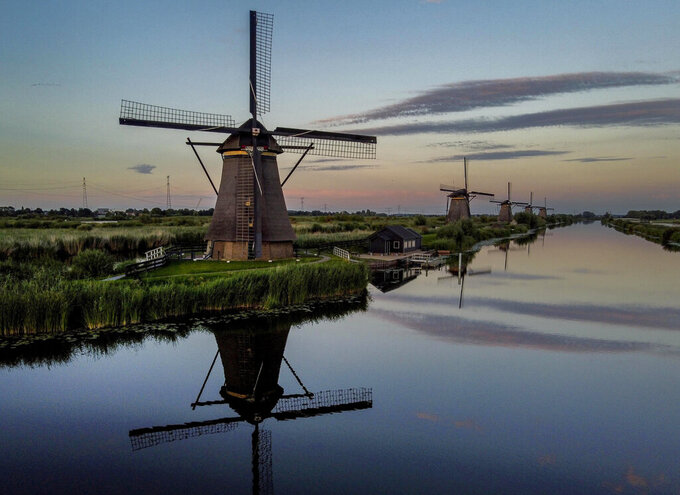 Windmills line a canal in Kinderdiijk, Netherlands, Saturday, Aug. 1, 2020. The five windmills are part of 19 mills built in the 18th century some 15 kms. (9.3 miles) south of Rotterdam. (AP Photo/Michael Probst)
