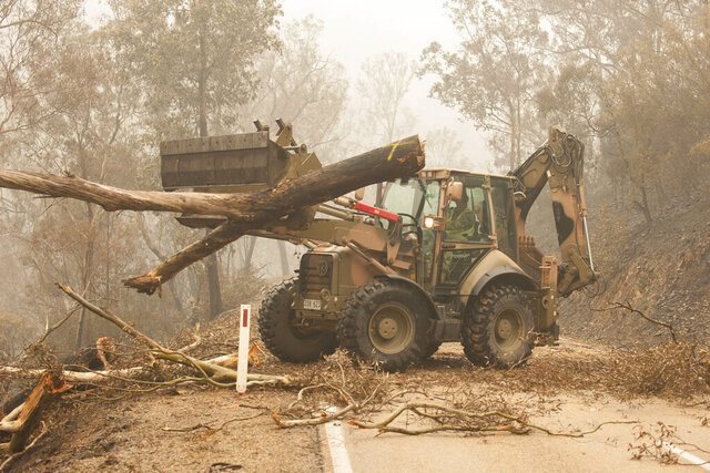 "In this image released and dated on Jan. 6, 2020, from Australian Department of Defence, plant operators Cpl. Duncan Keith and Sapper Ian Larner of the 22nd Engineer Regiment use a 434 backhoe to assist staff from Forestry Management Victoria to clear fire damaged trees from the great Alpine road between Bairnsdale and Omeo during Operation Bushfire Assist 19-20 in Bairnsdale, Victoria, Australia. Australia's government on Monday said it was willing to pay ""whatever it takes"" to help communities recover from deadly wildfires that have ravaged the country. (Department of Defence via AP)"