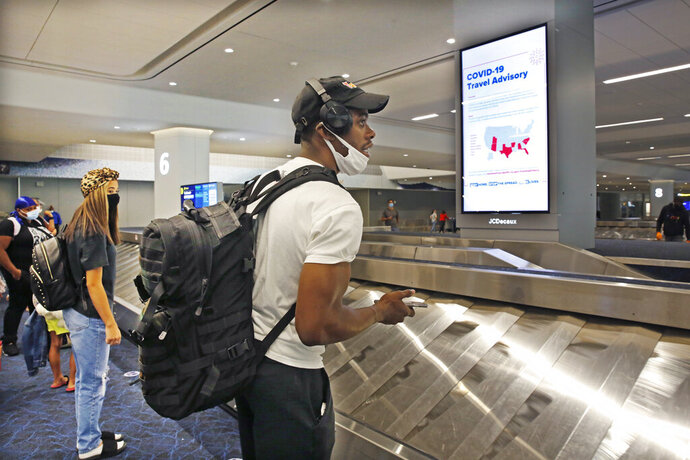 Arriving passengers await their bags in the baggage claim area at LaGuardia Airport's Terminal B baggage claim area, Thursday, June 25, 2020, in New York. New York, Connecticut and New Jersey are asking visitors from states with high coronavirus infection rates to quarantine for 14 days. (AP Photo/Kathy Willens)