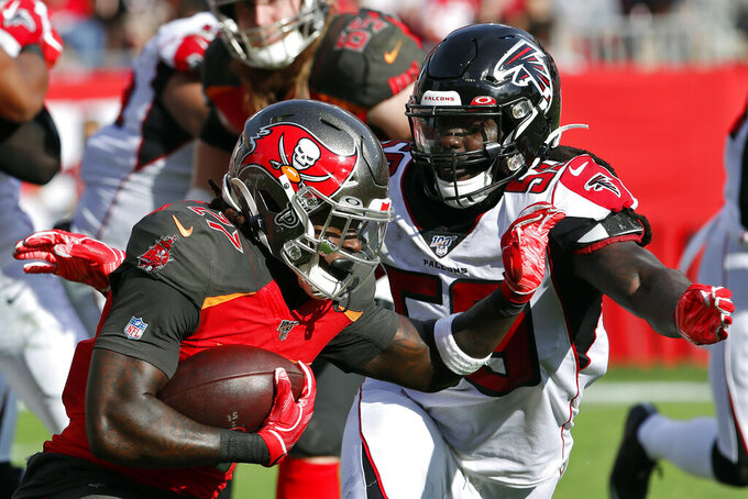 Atlanta Falcons outside linebacker De'Vondre Campbell (59) closes in on Tampa Bay Buccaneers running back Ronald Jones II (27) on a run during the second half of an NFL football game Sunday, Dec. 29, 2019, in Tampa, Fla. (AP Photo/Mark LoMoglio)