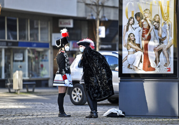 """Two women in costumes stand beside an advertising for 'Germany's next top model' tv show at the """"Alter Markt"""" where normally tens of thousands of revelers dressed in carnival costumes would celebrate the start of the street carnival in Cologne, Germany, Thursday, Feb. 11, 2021. This year all carnival celebrations are banned due to the coronavirus pandemic. (AP Photo/Martin Meissner)"""