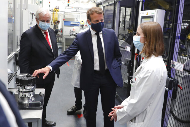 French President Emmanuel Macron, center, wearing a protective face mask, listens to explanations by an employee as CEO of France-based multinational automotive supplier Valeo Jacques Aschenbroicha looks on, in Etaples, , northern France, Tuesday May 26, 2020. Emmanuel Macron announced a 8 billion euro ($8.8 billion) plan to save the country's car industry from huge losses wrought by virus lockdowns, including a big boost for electric vehicles. The plan includes government subsidies for car buyers and longer-term investment in innovative technology, especially in battery-powered cars. (Ludovic Marin, Pool via AP)