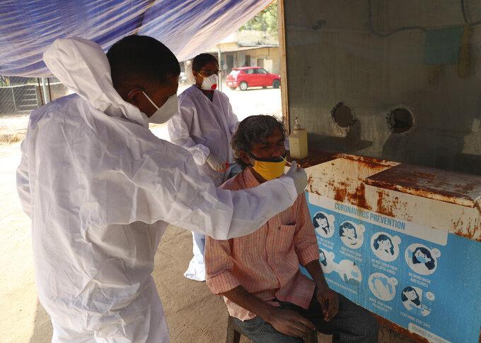 A health worker takes a nasal swab sample at a COVID-19 testing center in Hyderabad, India, Saturday, Jan. 2, 2021. (AP Photo/Mahesh Kumar A.)