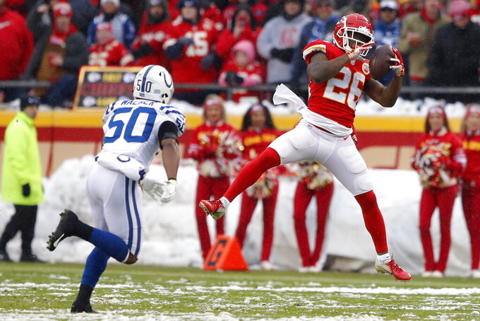 Kansas City Chiefs running back Damien Williams (26) makes a catch in front of Indianapolis Colts linebacker Anthony Walker (50) during the first half of an NFL divisional football playoff game in Kansas City, Mo., Saturday, Jan. 12, 2019. (AP Photo/Charlie Neibergall)