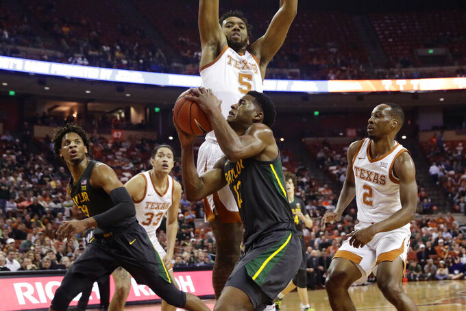 Baylor guard Jared Butler (12) drives to the basket against Texas forward Royce Hamm Jr. (5) during the first half of an NCAA college basketball game, Monday, Feb. 10, 2020, in Austin, Texas. (AP Photo/Eric Gay)