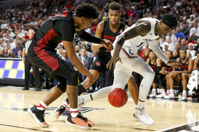 Houston Cougars guard Nate Hinton, left, and Cincinnati Bearcats forward Tre Scott, right, chase a loose ball in the first half of an NCAA college basketball game, Saturday, Feb. 1, 2020, in Cincinnati. (Kareem Elgazzar/The Cincinnati Enquirer via AP)