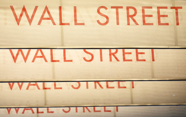 FILE - Signs for Wall Street are shown, Thursday, July 30, 2020, in New York.  Stocks are off to a weak start on Wall Street, Tuesday, Aug. 4  as investors keep a close eye on talks in Congress over the next installment of badly needed relief for people whose livelihoods and businesses were impacted by coronavirus lockdowns. (AP Photo/Mark Lennihan)