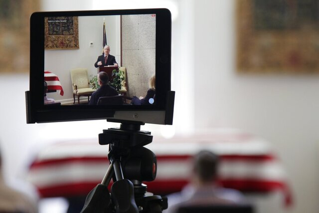 In this Friday, April 3, 2020, photo, a tablet livestreams the funeral of J. Robert Coleman in Lexington, S.C. Following CDC guidelines during the coronavirus outbreak, Thompson Funeral Homes asked Coleman's family to invite fewer than 10 people to his service. (AP Photo/Sarah Blake Morgan)