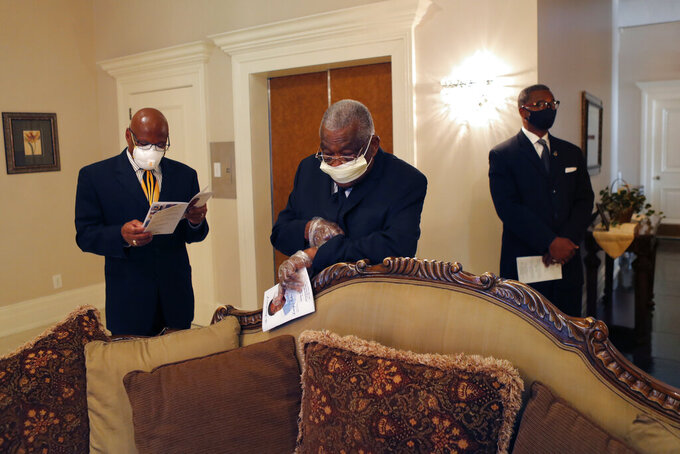 FILE - In this April 22, 2020, file photo, friends and family of Larry Hammond who were among only 10 mourners allowed, stand in the parlor at Boyd Funeral Home before his funeral in New Orleans. (AP Photo/Gerald Herbert, File)