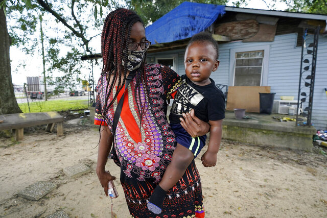 Fakisha Fenderson and her son Tyler stand in the front yard of her parent's home in Laurel, Miss., Monday, Aug. 31, 2020. Fenderson's weekly unemployment allotment is under $100, effectively eliminating her chance at receiving the $300 weekly supplement proposed by President Trump's executive order. (AP Photo/Rogelio V. Solis)