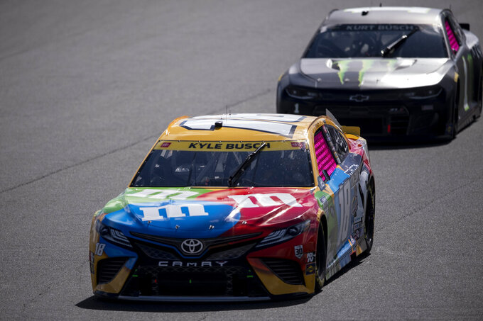 Kyle Busch (18) and Kurt Busch (1) compete during a NASCAR Cup Series auto racing race at Charlotte Motor Speedway, Sunday, Oct. 10, 2021, in Concord, N.C. (AP Photo/Matt Kelley)