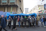 In this photo taken Sunday, Dec. 8, 2019, Iraqi protesters lineup by a volunteer chef to receive a free meal, in Tahrir square, Baghdad, Iraq. In Baghdad's Tahrir Square, there are the anti-government protesters demonstrating for a better future for Iraq, and there are the volunteers who feed them. From stuffed lamb and fish, to the giant pots of soups and rice to the plates of lentils and beans, there is no shortage of food to go around. Volunteers from the capital and southern provinces cook traditional dishes that reflect the country's rich cuisine and bring protesters together.  (AP Photo/Nasser Nasser)