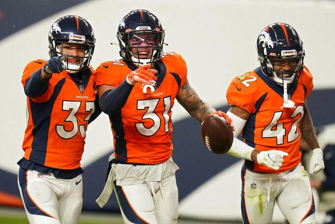 Denver Broncos safety Alijah Holder (33), free safety Justin Simmons (31) and cornerback Parnell Motley celebrate after Simmons made an interception against the Las Vegas Raiders during the second half of an NFL football game, Sunday, Jan. 3, 2021, in Denver. (AP Photo/Jack Dempsey)