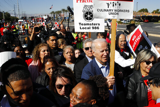 """FILE - In this Feb. 19, 2020, file photo, Democratic presidential candidate former Vice President Joe Biden walks on a picket line with members of the Culinary Workers Union Local 226 outside the Palms Casino in Las Vegas. Biden's tenure as Barack Obama's vice president is complicating his efforts to deepen ties with Latinos who could be critical to winning the White House. For many Latinos, Biden's embrace of the Obama years is a frightening reminder of when the former president ejected about 3 million people living in the U.S. illegally, earning him the moniker of """"deporter in chief."""" (AP Photo/Patrick Semansky, File)"""