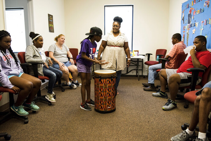 In this Thursday, June 27, 2019 photo, Jocelyn Stovall, of Evolve Music Therapy, has each student play on the drum while working with special needs children in Montgomery, Ala. (Jake Crandall/Montgomery Advertiser via AP)