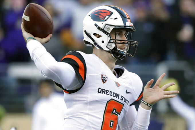 FILE - In this Nov. 17, 2018, file photo, Oregon State quarterback Jake Luton passes against Washington in the first half of an NCAA college football game, in Seattle. Luton will start for Oregon State. (AP Photo/Elaine Thompson, File)