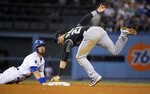 Los Angeles Dodgers' Cody Bellinger, left, dives back safely after advancing to second on a single by Matt Beaty as Colorado Rockies shortstop Trevor Story reaches for a tag during the seventh inning of a baseball game Tuesday, Sept. 3, 2019, in Los Angeles. (AP Photo/Mark J. Terrill)