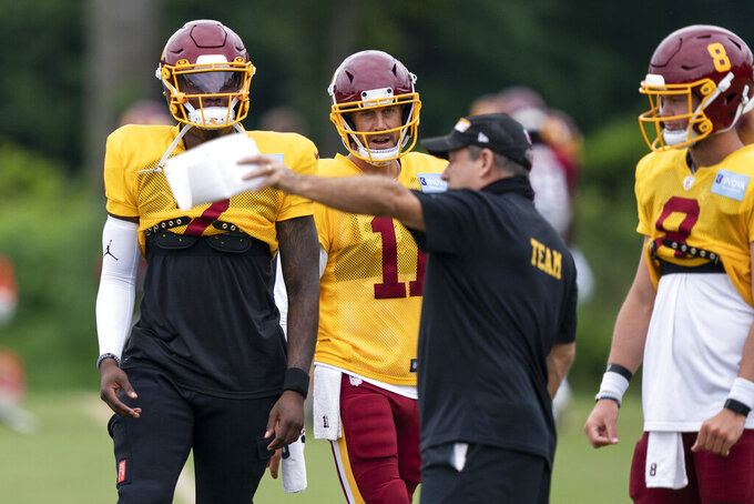 Washington quarterbacks Dwayne Haskins Jr., left, Alex Smith and Kyle Allen take direction during practice at the team's NFL football training facility, Wednesday, Aug. 19, 2020, in Ashburn, Va. (AP Photo/Alex Brandon)