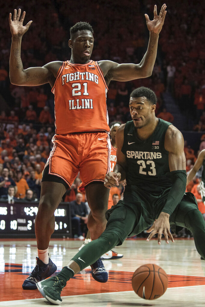 Michigan State's Xavier Tillman (23) moves the ball against Illinois' Kofi Cockburn (21) in the second half of an NCAA college basketball game, Tuesday, Feb. 11, 2020, in Champaign, Ill. (AP Photo/Holly Hart)