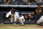 New York Yankees' Tyler Wade, left, scores a run behind Baltimore Orioles catcher Pedro Severino during the 10th inning of a baseball game on Friday, Sept. 3, 2021, in New York. (AP Photo/Adam Hunger)