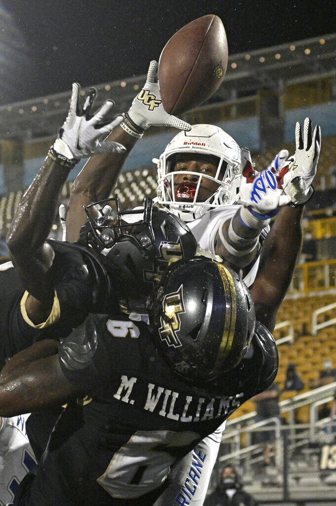 Tulsa safety TieNeal Martin (7) breaks up a pass in front of Central Florida wide receiver Amari Johnson (17) and wide receiver Marlon Williams (6) in the end zone on the final play of an NCAA college football game, Saturday, Oct. 3, 2020, in Orlando, Fla. (AP Photo/Phelan M. Ebenhack)