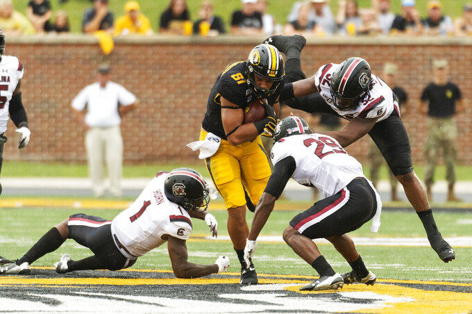 Missouri tight end Albert Okwuegbunam, center, is swarmed by South Carolina defensive back Jaycee Horn, left, Kingsley Enagbare, right, and J.T. Ibe during the third quarter of an NCAA college football game, Saturday, Sept. 21, 2019, in Columbia, Mo. (AP Photo/L.G. Patterson)