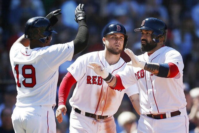 Boston Red Sox's Sandy Leon, right, celebrates his three-run home run that also drove in Michael Chavis, center, and Jackie Bradley Jr. (19) during the third inning of a baseball game against the Seattle Mariners in Boston, Saturday, May 11, 2019. (AP Photo/Michael Dwyer)