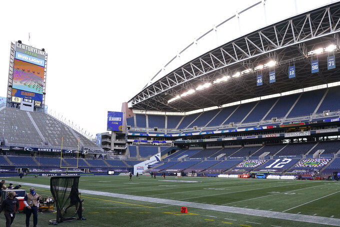 Both the old (CenturyLink Field, left) and new (Lumen Field, right) names stand in the stadium where the Seattle Seahawks NFL football team plays, before a game between the Seahawks and the Arizona Cardinals, Thursday, Nov. 19, 2020, in Seattle. The field name was changed because CenturyLink, the current field name rights-holder, has rebranded to Lumen Technologies. (AP Photo/Elaine Thompson)