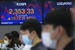 Currency traders watch monitors at the foreign exchange dealing room of the KEB Hana Bank headquarters in Seoul, South Korea, Friday, Aug. 7, 2020. Asian shares were mostly lower Friday in lackluster trading, as the region weighed continuing trade tensions over China and optimism about more fiscal stimulus for the ailing U.S. economy. (AP Photo/Ahn Young-joon)